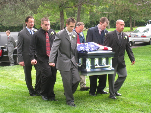 The pallbearers carry the casket to the grave site.