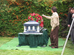 Pallbearer lays his flower on the casket.
