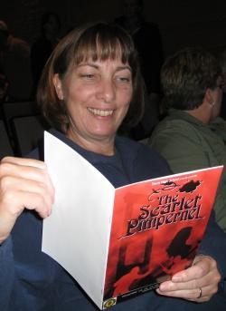 Jill holding a program.