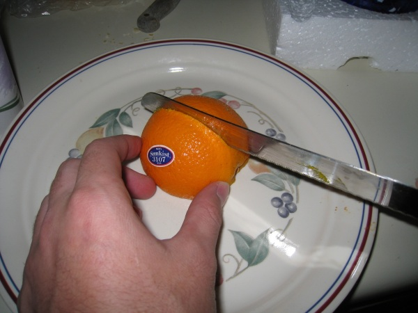 Turn the orange on its face to cut in two