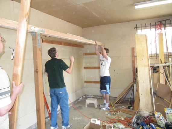 Paul and Jake install the first plywood sheet for the garage shelves